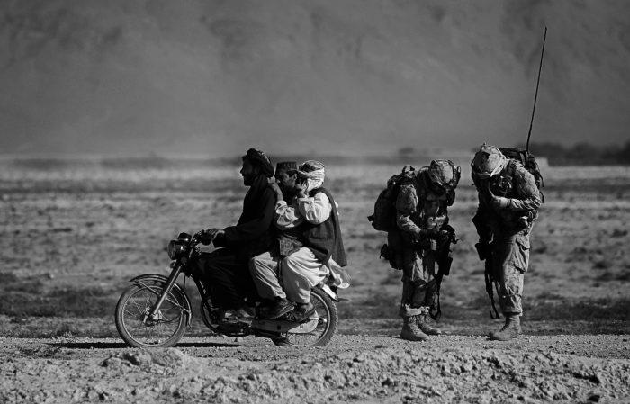 Afghanische Männer auf einem Motorrad überholen kanadische Soldaten auf einer Patrouille im Bezirk Panjwayi; Salavat, Afghanistan, September 2010Pigmentdruck auf Barytpapier29,7 x 42 cmKunstpalast, Düsseldorf © picture alliance / AP Images
